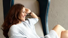 Sexy junge hübsche Frau, welche die blaue Wolljacke sitzt auf einem Stuhl trägt stock footage