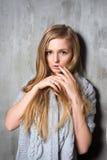 Sexy junge langhaarige Blondine in der gestrickten Strickjacke, die gegen grungy graue Wand aufwirft Das erschrockene oder aufgeb Stockfotografie
