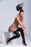 Sexy junge Modefrau, die auf einem weißen Stuhl sitzt lizenzfreies stockbild