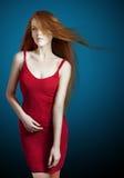 Sexy junge rote Haarfrau in einem roten Kleid Stockfotografie