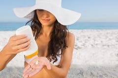 Sexy junger Brunette, der um ihrem Körper sich setzt auf Sonnencreme sich kümmert Lizenzfreie Stockfotos