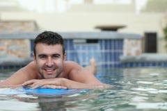 Sexy junger Mann, der auf eine Matratze im Wasserpool schwimmt Lizenzfreies Stockbild