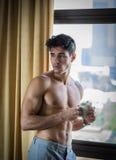 Sexy junger Mann durch Fenster mit Kaffeetasse Stockfoto