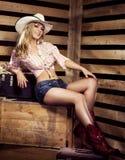 Sexy junges blondes Cowgirl mit dem Sitzkörper, der auf Bauernhof lächelt Stockfotos