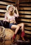 Sexy junges blondes Cowgirl mit dem Sitzkörper, der auf Bauernhof lächelt Lizenzfreie Stockbilder