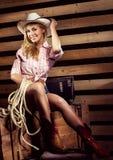 Sexy junges blondes Cowgirl mit dem Sitzkörper, der auf Bauernhof lächelt Stockfotografie