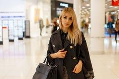 Sexy junges blondes Frauenmodell in einem schicken modernen Mantel mit einer modernen ledernen schwarzen Modehandtasche lizenzfreies stockbild