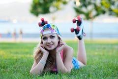 Sexy junges blondes Mädchen in den Weinleserollen, die auf Rasen im Park liegen und Musik auf Kopfhörern hören Lizenzfreie Stockfotos
