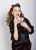 Sexy junges blondes mit dem langen gelockten Haar in einem schwarzen Tupfenkleid, setzte ihren Zeigefinger zu ihren roten Lippen Lizenzfreie Stockfotografie