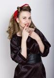 Sexy junges blondes mit dem langen gelockten Haar in einem schwarzen Tupfenkleid, setzte ihren Zeigefinger zu ihren roten Lippen Stockfotografie