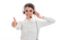 Sexy junges Call-Center-Büromädchen mit den Kopfhörern und Mikrofon, welche die Kamera lächelnd und Daumen zeigend betrachtet Lizenzfreie Stockfotografie