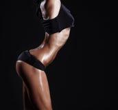 Sexy junges Eignung Brunettemädchen mit Muskeln, das über schwarzem Hintergrund aufwirft stockfoto