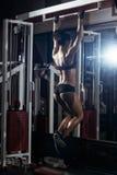 Sexy junges Eignungsmädchen zieht in der Turnhalle hoch Stockbilder