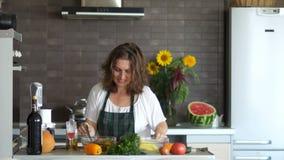 Sexy junges Hausfrautanzen in der Küche und Gesang in einem Mischer Eine Frau in der großen Stimmung, die einen Salat zubereitet  stock video
