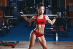 Sexy junges Leichtathletikmädchen, das mit Barbell auf ihren Schultern aufwirft Stockfotos