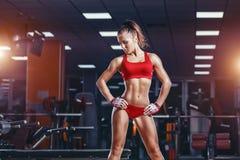 Sexy junges Leichtathletikmädchen, das nach Eignungsschulungsübungen in der Turnhalle stillsteht Stockbild