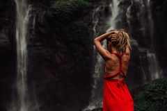 Sexy junges Mädchen im roten Kleid an überraschendem Wasserfall Bali - die beste Kaskade in Indonesien stockfotografie