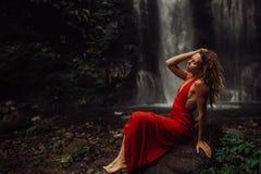 Sexy junges Mädchen im roten Kleid an überraschendem Wasserfall Bali - die beste Kaskade in Indonesien stockfotos