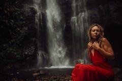 Sexy junges Mädchen im roten Kleid an überraschendem Wasserfall Bali - die beste Kaskade in Indonesien lizenzfreies stockfoto