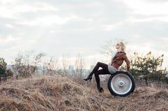 Sexy junges Mädchen sitzt auf einem großen Rad Lizenzfreie Stockbilder