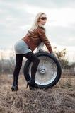 Sexy junges Mädchen sitzt auf einem großen Rad Lizenzfreies Stockbild