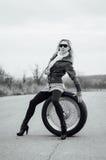 Sexy junges Mädchen sitzt auf einem großen Rad Stockfoto