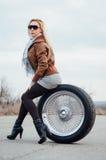 Sexy junges Mädchen sitzt auf einem großen Rad Stockfotos