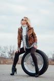 Sexy junges Mädchen sitzt auf einem großen Rad Lizenzfreies Stockfoto