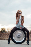 Sexy junges Mädchen sitzt auf einem großen Rad Stockfotografie