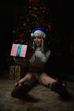 Sexy junges Mädchen hat Geschenk unter Weihnachtsbaum empfangen Lizenzfreie Stockfotos