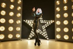 Hot slim woman posing in latex rubber fashion clothes on black background with yellow lights bulbs. Kinky woman in fetish fashion cose catsuit with corset royalty free stock photography