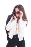 Sexy and kinky young business woman posing on white studio. Wearing suit with open shirt and sunglasses or shades Royalty Free Stock Image