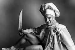Sexy Koch, der auf einer Tabelle mit einem Messer sitzt stockfotografie