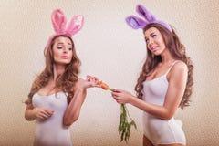 2 sexy konijntjesmeisje met konijntjesoren en wortel Stock Fotografie
