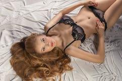 Sexy krullende gilr in zwarte lingerie Stock Fotografie