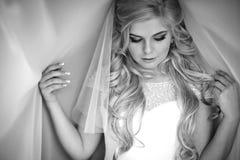 Sexy lächelnde blonde Braut, die im Hochzeitskleid unter weißem Cu aufwirft stockbild