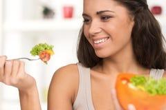 Sexy lächelnde Frau, die Salat isst Stockbild