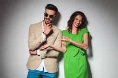 Sexy lachende Modefrau, beim Zeigen auf ihren Mann, Stockfotografie