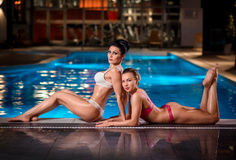 Sexy ladies posing near pool Stock Images