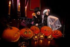 Sexy ladies vampire. Halloween concept: sexy ladies vampire with halloween pumpkins over red background Royalty Free Stock Image