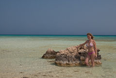 Sexy lady in bikini near a rock in red sea. Lady in bikini in a tropical trasparent sea, touching a big stone water Stock Photography