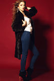 Sexy lady with blond curly jair  in blue jeans and black fur coat Royalty Free Stock Photos