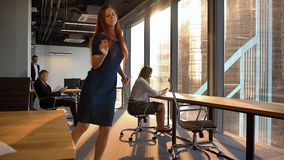 lady employee happy dancing inside of modern office