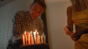 lady and handsome guy lights candles on tasty birthday cake. Prepearing for party. stock video