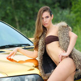 Sexy lady near the golden car. Beautiful sexy girl in bikini and in fur cape posing on a background of golden car. sexy lady near the golden car Royalty Free Stock Photos