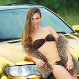 Sexy lady near the golden car. Beautiful sexy girl in bikini and in fur cape posing on a background of golden car. sexy lady near the golden car Royalty Free Stock Image