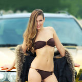 Sexy lady near the golden car. Beautiful sexy girl in bikini and in fur cape posing on a background of golden car. sexy lady near the golden car Stock Photography