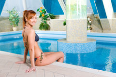 Lady at swimming pool. Happy young woman sitting on the edge of pool. She's smiling and looking at camera royalty free stock image