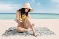 Sexy lady using sunscreen at beach Royalty Free Stock Photography