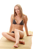 Sexy lady wearing swimsuit on bamboo mat Royalty Free Stock Image
